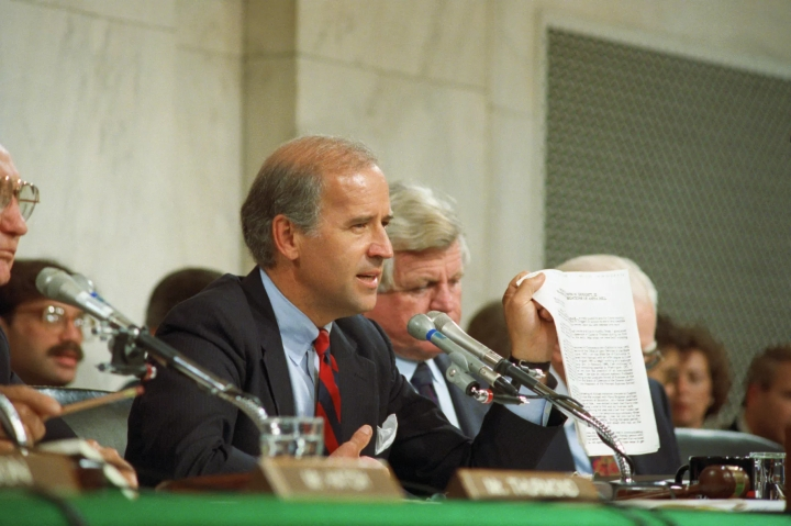 Senate Judiciary Committee Chair Joe Biden holds up a copy of the FBI report on Anita Hill during committee hearings as Biden questions Hill about her allegations against Judge Clarence Thomas in 1991.